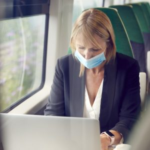 businesswoman-on-train-working-on-laptop-wearing-ppe-face-mask-during-health-pandemic.jpg
